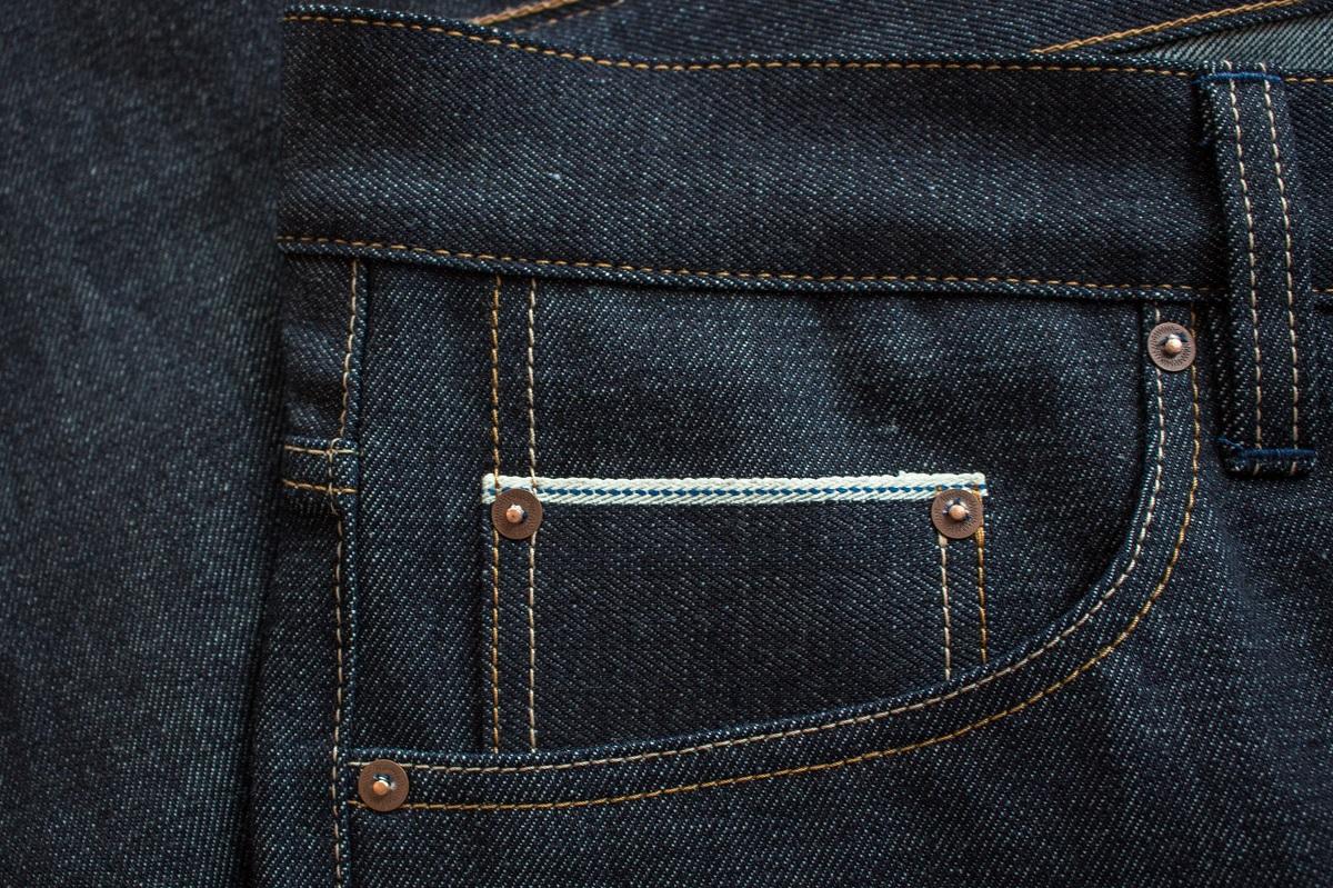 Produktmerkmale sind die historische Webkante, Kappnähte, extra verstärkte Gesäßtaschen mit verdeckten Taschennieten, ungewaschen.
